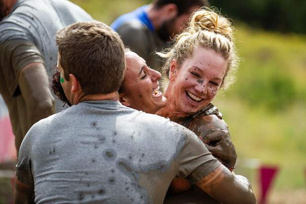 Tough Mudder teammates embrace after making it through the mud.