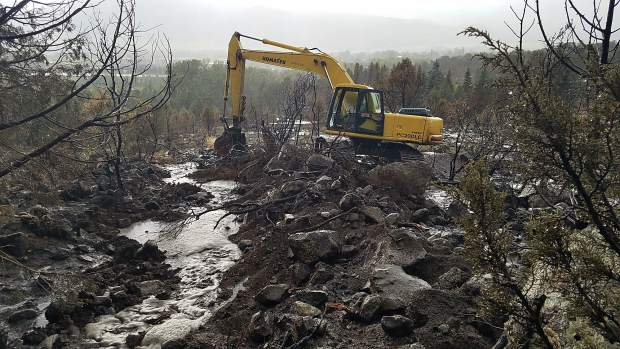 Excavating on the Lane Tree Farm property on Saturday during a storm creating a mudslide on the Lake Christine Fire burn scar.
