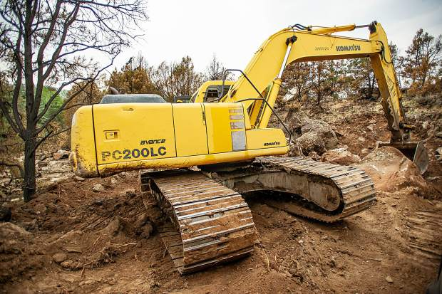 An excavator on the Lane family's property that has been used to create trenches to divert water from future flash flooding episodes on the Lake Christine burn scar on Wednesday afternoon.