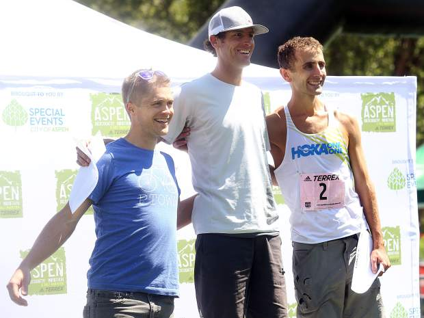 Aspen Backcountry Marathon winner Joshua Eberly, center, stands on the podium with runner-up David Roche, right, and third-place finisher Michael Barlow on Saturday, Aug. 11, 2018, at Rio Grande Park. (Photo by Austin Colbert/The Aspen Times).