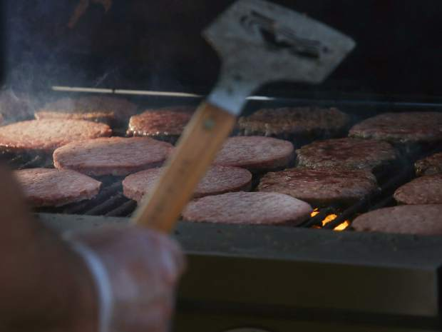 Hamburgers are grilled during the National Night Out event on Tuesday, Aug. 7, 2018 at Triangle Park in Willits.