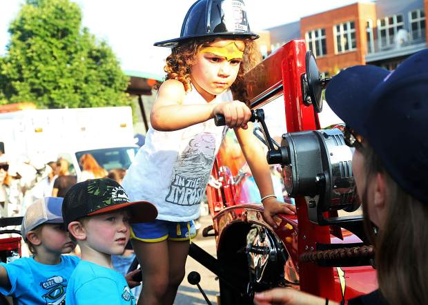 Colette Abraham, 4, learns how to operate the siren on an antique Basalt fire truck during the National Night Out event on Tuesday, Aug. 7, 2018 at Triangle Park in Willits.