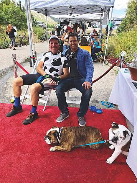 Two sets of besties: Martin Davis and Josh Landis (seated) and Pancake and Flash the bulldogs (lounging) at the Aspen Animal Shelter.