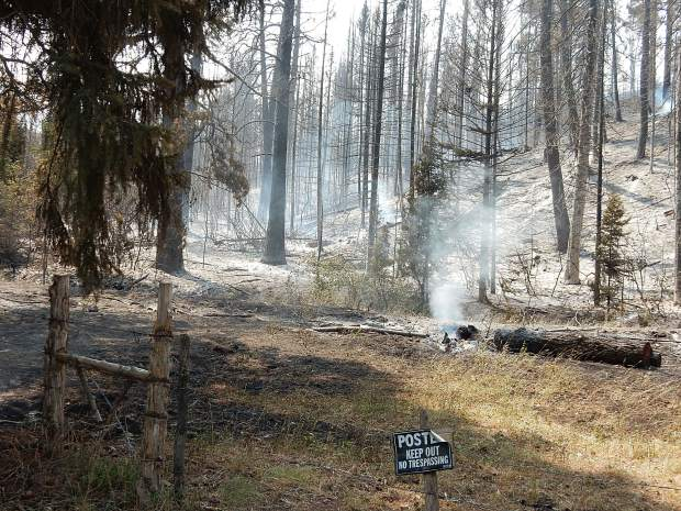 A log smoulders Thursday after a finger of the Cabin Lake Fire near Meeker snaked down to the southeast of the main blaze.