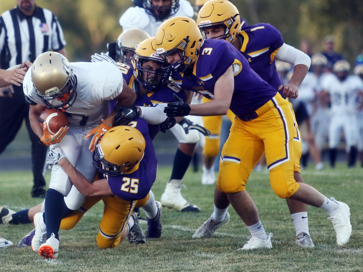 The Basalt defense gang tackles an Olathe runner in the first half of Friday's game. (Photo by Austin Colbert/The Aspen Times).