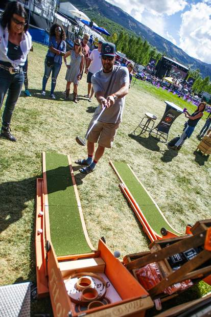 Denver resident Marc Anderson takes a putt at the Tito's Vodka booth on Saturday during the JAS Labor Day Experience on Saturday.