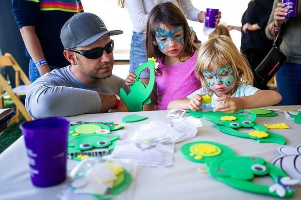 Chris Hatcher and his daughters Melanie, 5, and Emma, 2, create frog crafts in the vendor village at the JAS Labor Day Experience on Saturday.