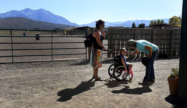 Beth Gusick, program coordinator and head riding instructor with WindWalkers, says goodbye to Grace McGlade, 3, and her mother, Lisa, of New Castle after wrapping up their therapy session.