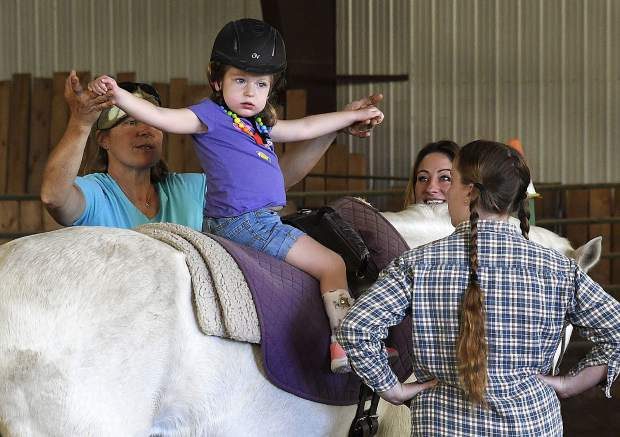 Beth Gusick, program coordinator and head riding instructor, works on movement and flexibility with WindWalkers client Grace McGlade, 3, of New Castle during a therapy session in Missouri Heights. Lisa McGlade, Grace's mother, said pregnancy complication and an injury during labor left her daughter unable to walk.