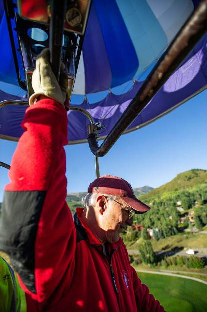Colorado Springs Pilot Stephen Blucher peers over the edge of his balloon