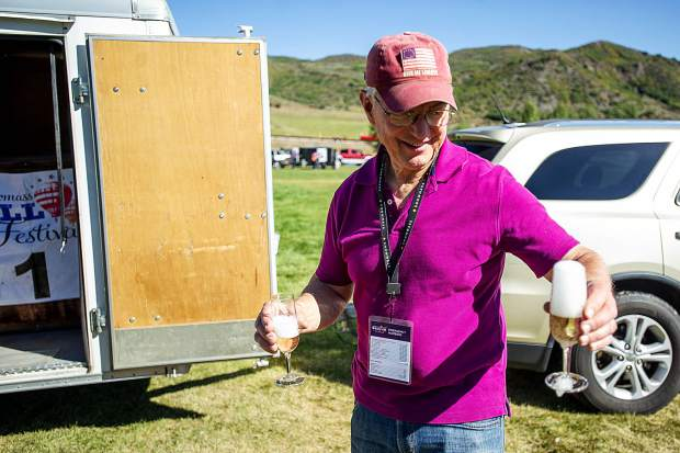 Colorado Springs Pilot Stephen Blucher holds out an overflowing glass of champagne after a successful flight on Friday for the 43rd annual Hot Air Balloon Festival in Snowmass.