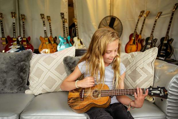 Hazel Miner, 9, test out a ukelele in the D'Angelico Guitars tent before the concerts at the Jazz Labor Day Experience on Friday.