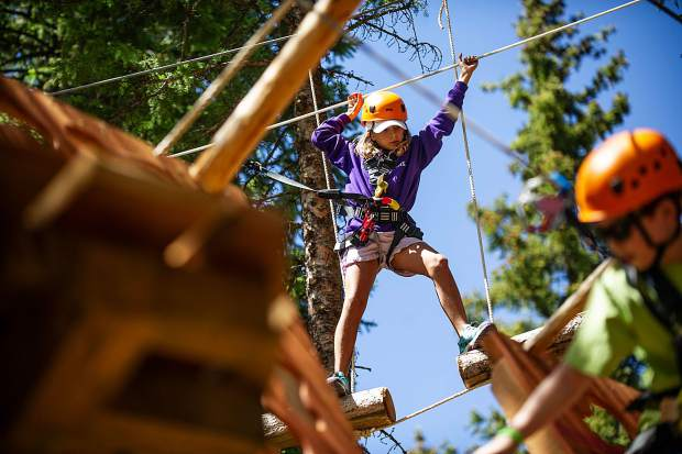 Caroline Goulandris, 10, on the ropes course treeline challenge on the opening day of the Lost Forest in Snowmass earlier this summer.