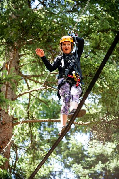 Chloe McGann, 12, crosses a tight rope in the Lost Forest Treeline Challenge course on Aug. 17 in Snowmass.
