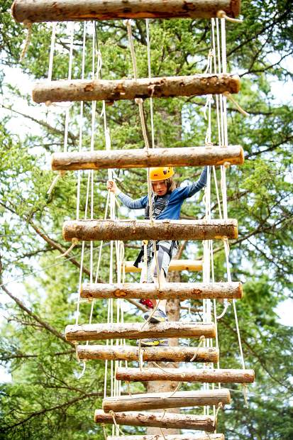 Felix, 9, crosses a log bridge on the treeline challenge course in Snowmass for opening day earlier this summer.