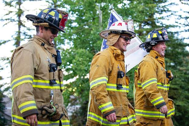Snowmass Firefighter Gregor Dekleva, left, Basalt Fire Division Chief Richard Cornelius, center, and Shaun Norris of Basalt Fire lead the 3rd annual Axes and Arms 9/11 climb on Brush Creek Road in Snowmass on Tuesday night. The event was to honor those who lost their lives on 9/11/2001, and the lives of all whom have made the ultimate sacrifice of service before and since. Hikers and first responders hiked to the same elevation that the brave men and women of FDNY did in the first