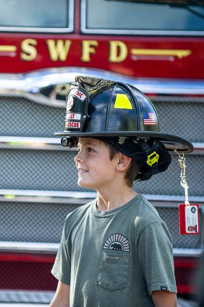 Ryder Cohan, 10, wears his father, Chris' firehat Tuesday night at the 3rd Annual Axes and Arms 9/11 Climb. The event was to honor those who lost their lives on 9/11/2001, and the lives of all whom have made the ultimate sacrifice of service before and since. Hikers and first responders hiked to the same elevation that the brave men and women of FDNY did in the first tower of The World Trade Center, gaining 956ft of elevation over 3 miles. The climb began at the Snowmass Town Park and finished at the Top of the Village Condos.