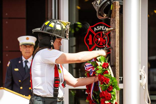 Aspen Firefighter Erin Smiddy hangs a wreath on a piece of North Tower steel adorned with a firefighter's helmet outside of the Aspen Fire Department on Tuesday for the 17th anniversary annual day of remembrance.