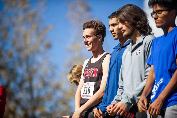 Aspen High senior Everett Olson, left, smiles at the crowd at the state regional cross country meet at the Aspen Golf Course on Friday morning. Olson took 5th overall.