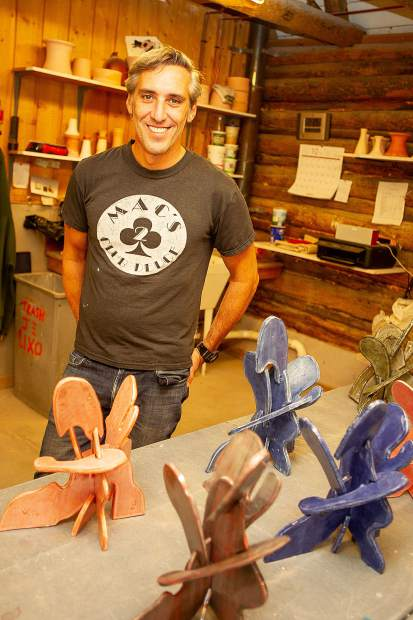 Artist Emilio Perez in front of his ceramic creations from Anderson Ranch.