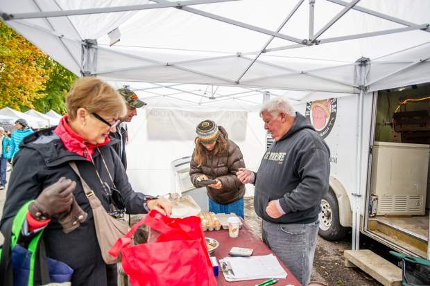 George Burkhardt, owner of Homestead Meat in Delta, helps customers at the Aspen Saturday Market.