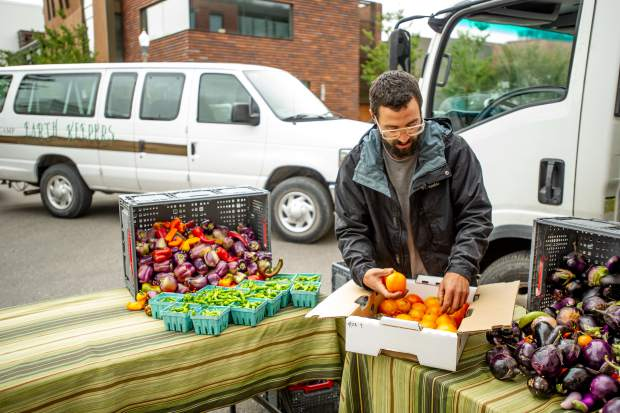 David Sutula of the Zephyros farm and garden booth sets up at the last farmers market of the season in Aspen on Oct. 6.
