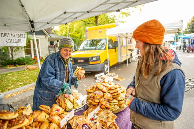 Dana Whitcomb serves patron Alyssa Barsanti at her Mountain Oven booth out of Paonia at the last Aspen farmers market for the season on Oct 6.