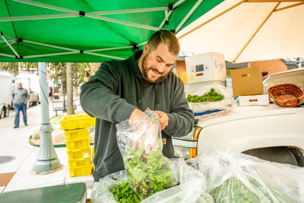 Andrew Gagnon measures out a bag of lettuce at the Borden Farm booth at the last Aspen farmers market for the season on Oct 6.