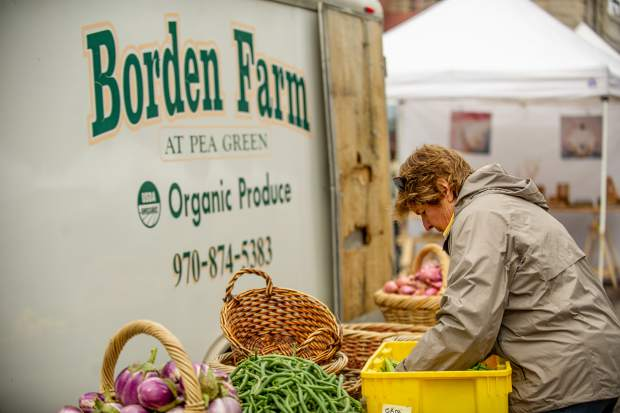 Pam Cunningham unloads produce for the Borden Farm booth at the last farmers market of the season in Aspen on Oct. 6.