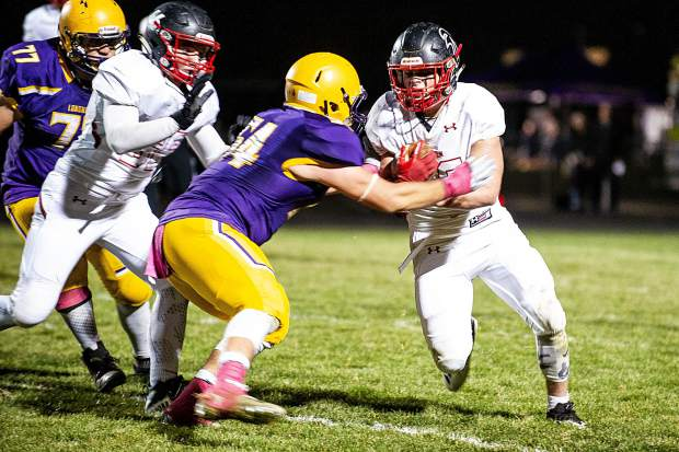 Trey Fabrocini, right, carries the ball for the Aspen Skiers versus Basalt on Friday night. Basalt won 27-6.