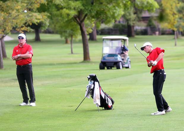 Aspen junior Jack Pevny hits his approach shot on the 18th hole as assistant coach Don Buchholz watches in the Class 3A state golf tournament on Tuesday, Oct. 2, 2018 at Boulder Country Club.