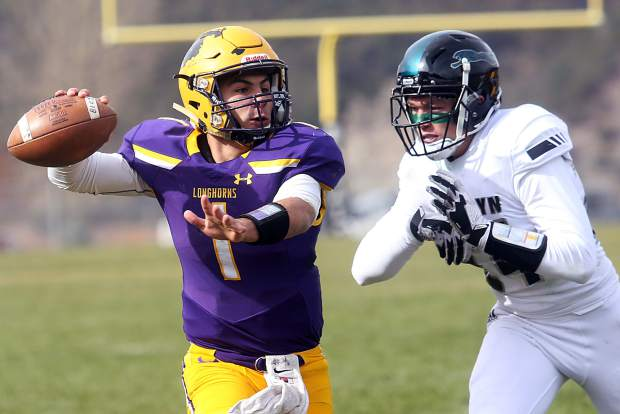 Basalt senior quarterback Trevor Reuss eyes a receiver downfield while being pressued by a D'Evelyn defender on Saturday, Nov. 3, 2018, in Basalt. (Photo by Austin Colbert/The Aspen Times).