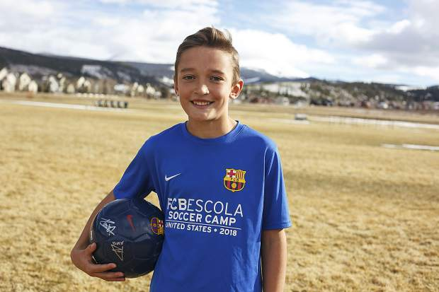 Summit Middle School sixth-grade student Nico Novotny, 11, poses for a photo with his FC Barcelona soccer ball while wearing his FC Barcelona camp gear on Friday at the field at Summit High School in Breckenridge.