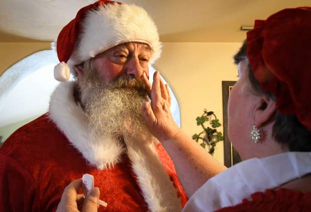 Kim Antonelli's wife Waynetta applies red make-up to give the appearance of a rosey-red faecd Santa.