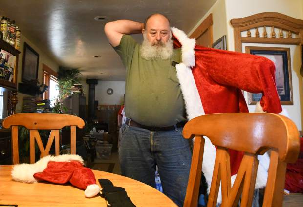 Kim Antonelli puts on his handmade Santa suit to prepare for a even as Mr.Claus at a private party.
