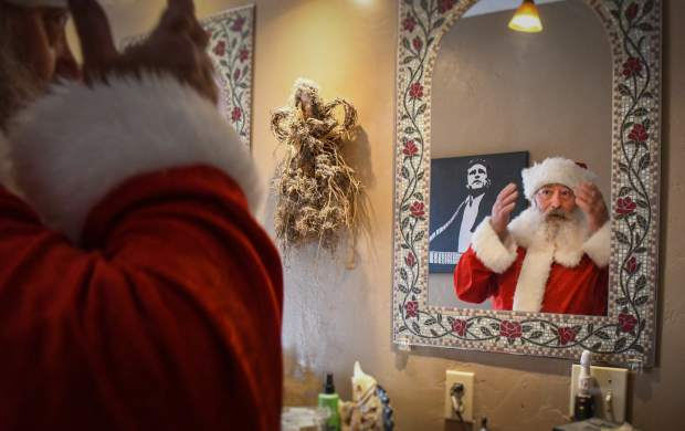 Kim Antonelli adjusts his hat in the mirror while preparing for an evening as Santa at a private party.