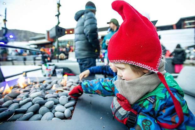 Spencer Sinclaire, 3, lights his marshmellow stick on fire in the plaza at Base Village in Snowmass on Saturday.
