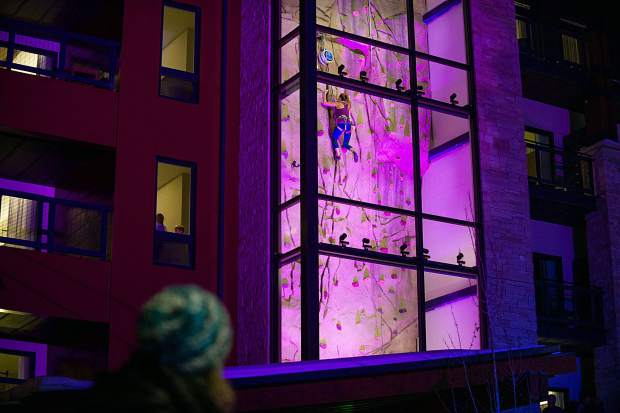 A rock climber ascends the wall on the Limelight Hotel in Snowmass on Saturday night.