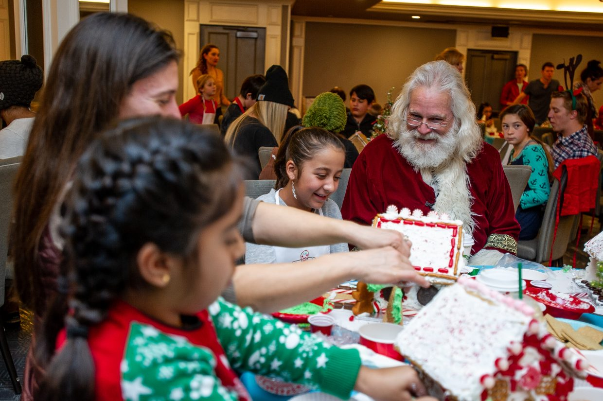 Alison Chaparro, 10, shares a laugh with Santa while decorating her gingerbread house at the 6th annual Buddy Program event held at the Little Nell on Saturday afternoon.