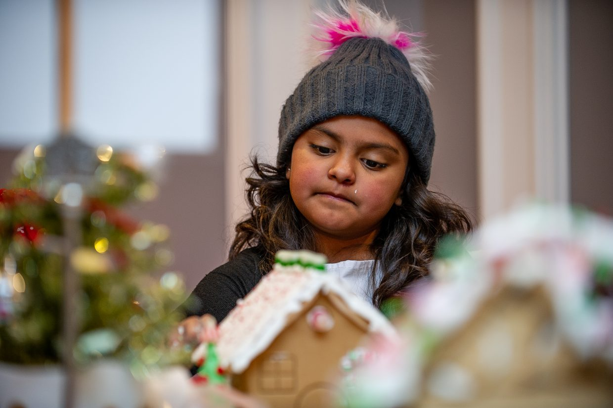 Debbie Morales, 8, decorates her gingerbread house at the 6th annual Buddy Program event held at the Little Nell on Saturday afternoon.