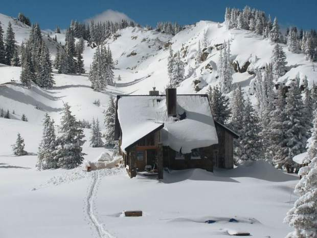 The Fowler-Hilliard Hut rests under a blanket of snow.