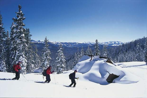 Three skiers make their way to the snow-covered Margy's Hut northeast of Aspen.