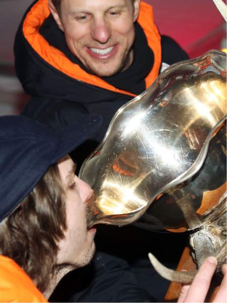 With help from Super G! team captain Edouard Gerschel, Ben Throm takes a gulp from the trophy after they won the Audi Ajax Cup on Sunday, Dec. 30, 2018, on Aspen Mountain.