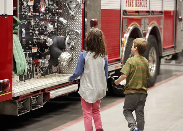 Kids explore the fire trucks on Friday, Nov. 30, 2018, during the dedication ceremony for the new Snowmass-Wildcat Fire Protection District fire station in Snowmass Village. (Photo by Austin Colbert/The Aspen Times)