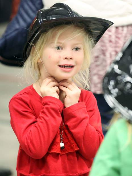 A young girl tries on a plastic firefighter helmet on Friday, Nov. 30, 2018, during the dedication ceremony for the new Snowmass-Wildcat Fire Protection District fire station in Snowmass Village. (Photo by Austin Colbert/The Aspen Times)
