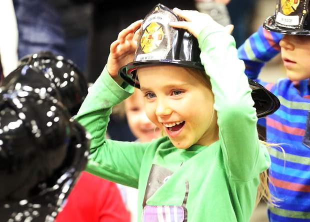 Maddy Blasberg, 5, tries on a plastic firefighter helmet Friday, Nov. 30, 2018 during the dedication ceremony for the new Snowmass-Wildcat Fire Protection District fire station in Snowmass Village. (Photo by Austin Colbert/The Aspen Times)