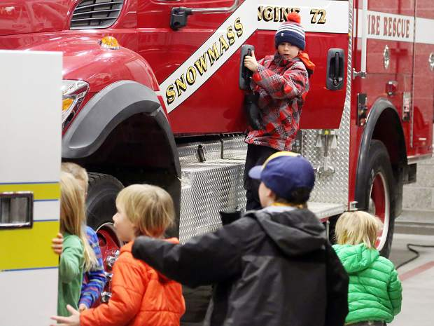 Kids play with the fire trucks on Friday, Nov. 30, 2018, during the dedication ceremony for the new Snowmass-Wildcat Fire Protection District fire station in Snowmass Village. (Photo by Austin Colbert/The Aspen Times)