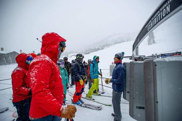 Aspen Ski Co. CEO Mike Kaplan, right, keeps order of skiers and snowboarders in line at the Exhibition lift at Aspen Highlands for opening day on Saturday.