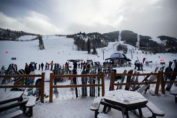 Skis and snowboards line the fence at the Aspen Highland's Ale House on Saturday for opening day.