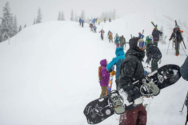 Nick Becker, front, and other skiers and snowboarders hike up Highland Bowl on Saturday for opening day.